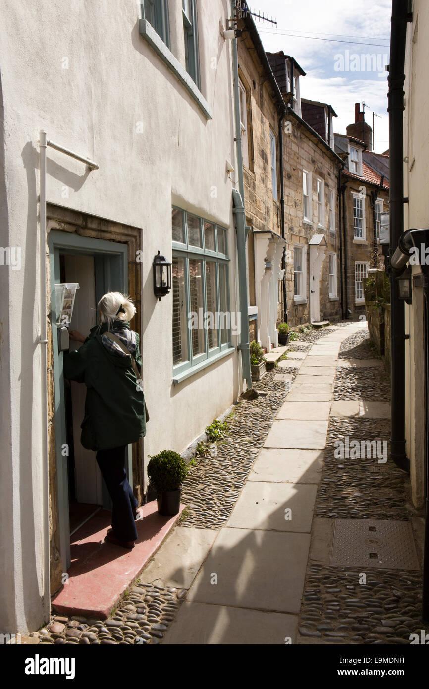UK, England, Yorkshire, Robin Hood's Bay, Lower Village visitor entering rented holiday house - Stock Image