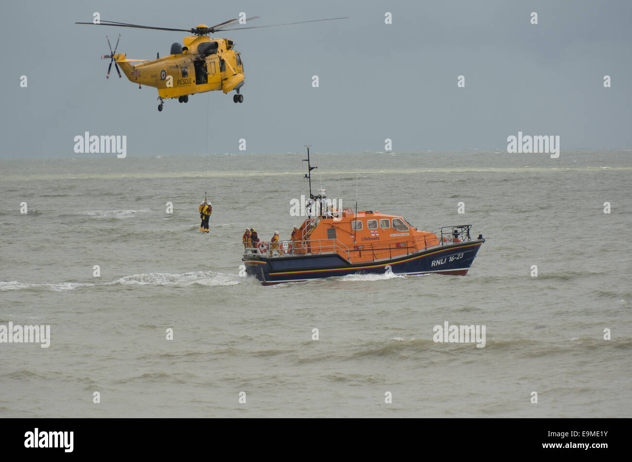 A Royal Air Force Sea King helicopter completes a training exercise by returning two RNLI volunteers to the Eastbourne - Stock Image