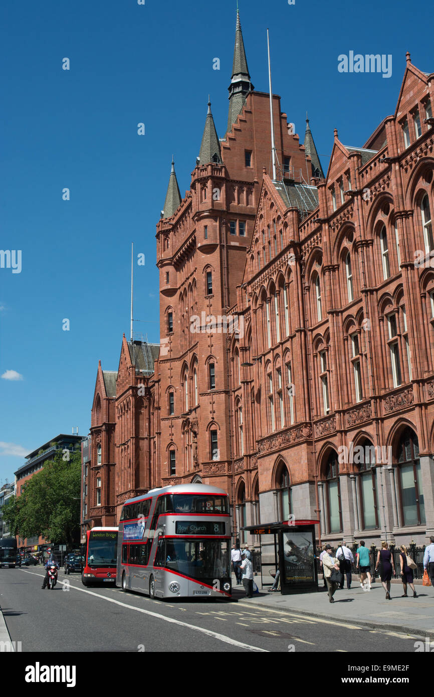 A silver New bus for London Routemaster passes in front of the former Prudential office in Holborn London - Stock Image
