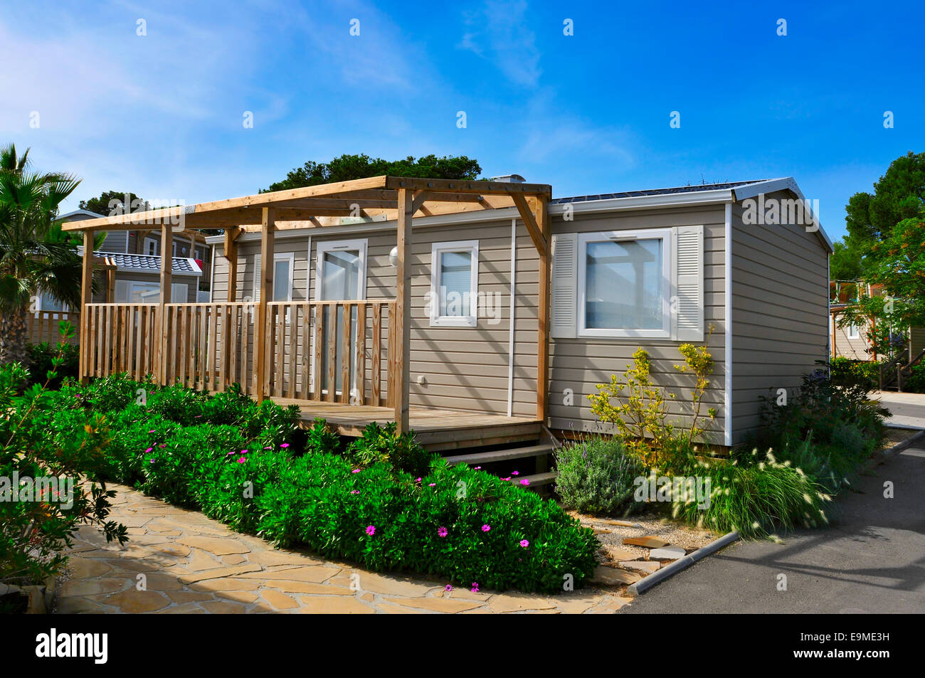 a nice mobile home with a wooden veranda in a campsite - Stock Image