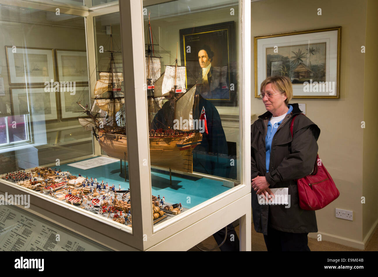 UK, England, Yorkshire, Whitby, Grape Lane, Captain Cook Museum, visitor looking at model of HMS Resolution - Stock Image
