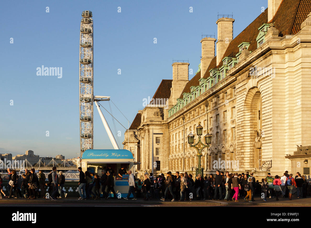 Crowds cross Westminster Bridge with the London Eye and County Hall behind, London, England,UK - Stock Image