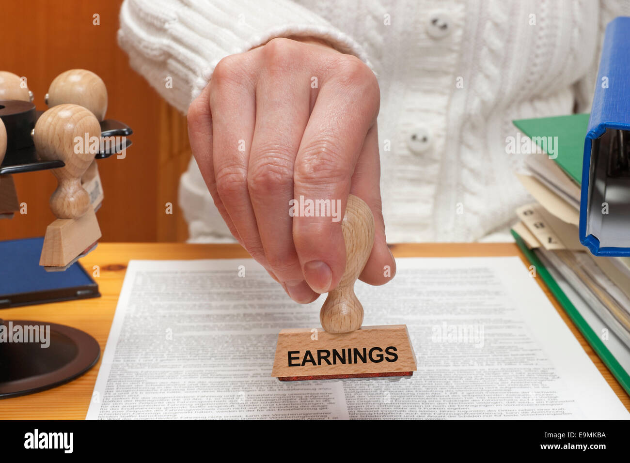 A stamp with the inscription earnings is held in the hand - Stock Image