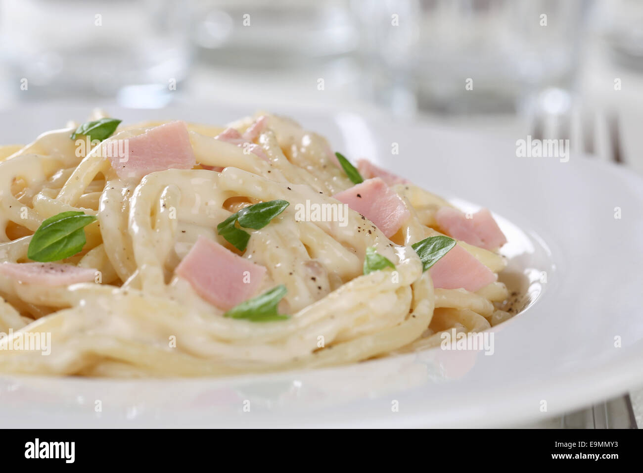 Spaghetti Carbonara noodles pasta meal with ham on a plate - Stock Image