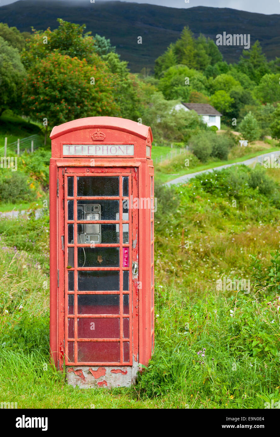 Old weathered red telephone kiosk in Scotland - Stock Image