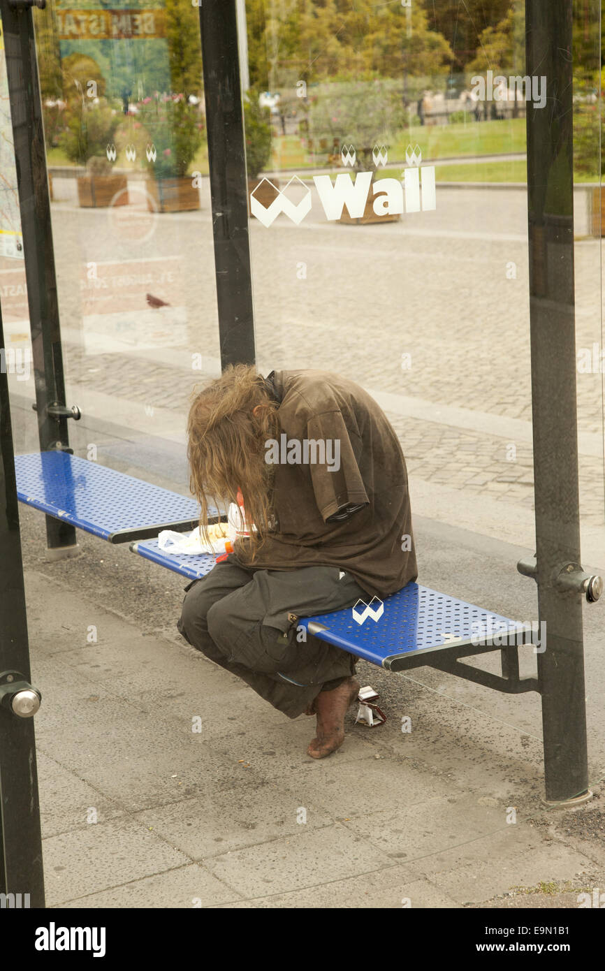 Disheveled, homeless and mentally ill man at a  bus stop in Berlin, Germany. - Stock Image