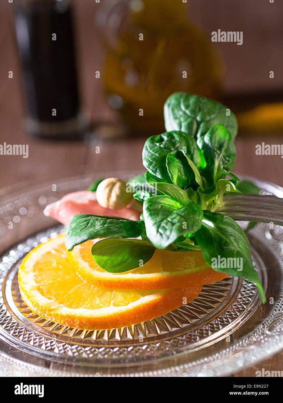 Lamb's lettuce with oranges and ham Stock Photo