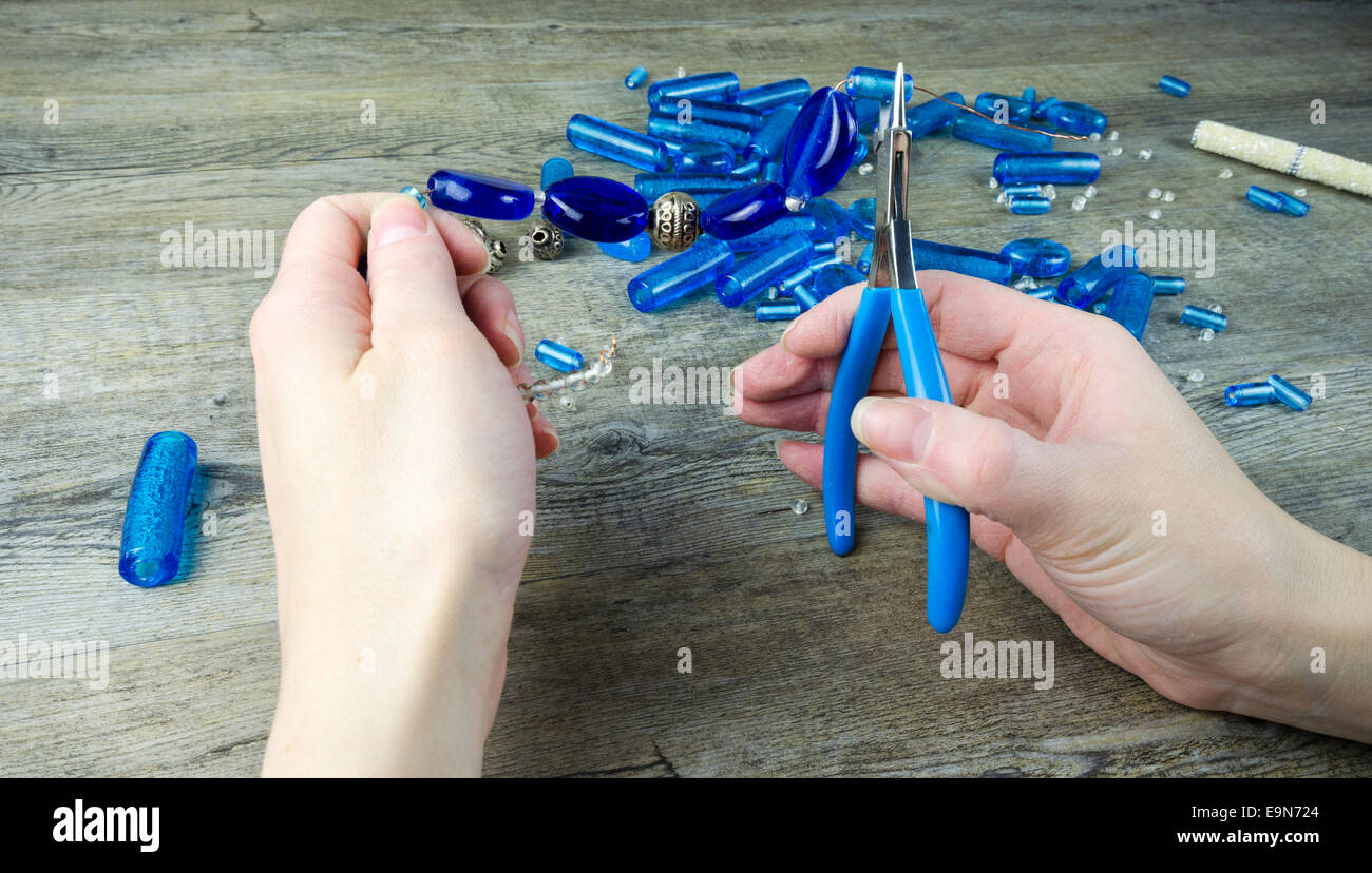 Woman's hands making a necklace from glass beads - Stock Image
