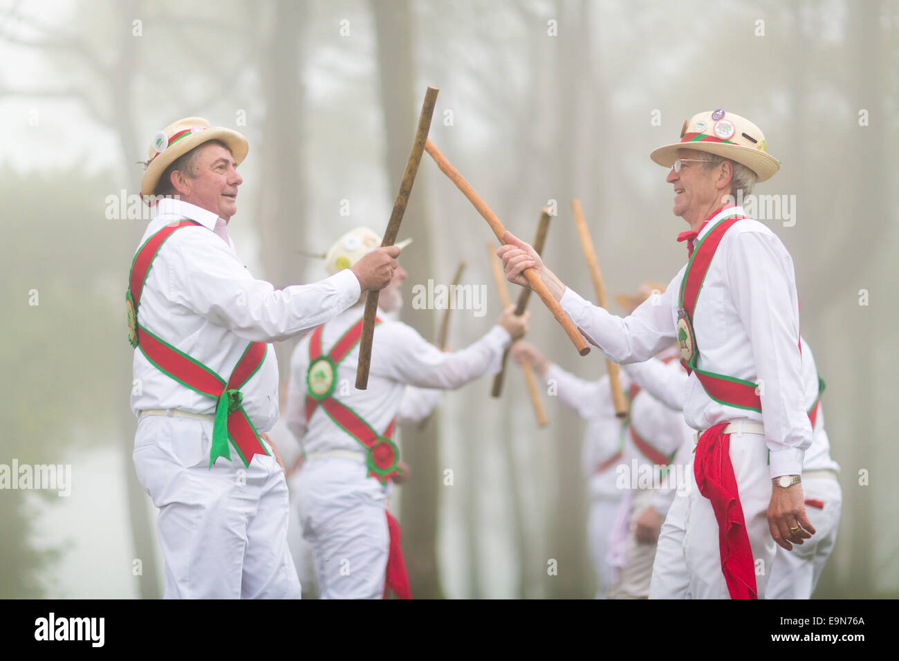 In thick fog and accompanied by the singing of cuckoos, Chanctonbury Ring Morris Men perform their traditional May - Stock Image