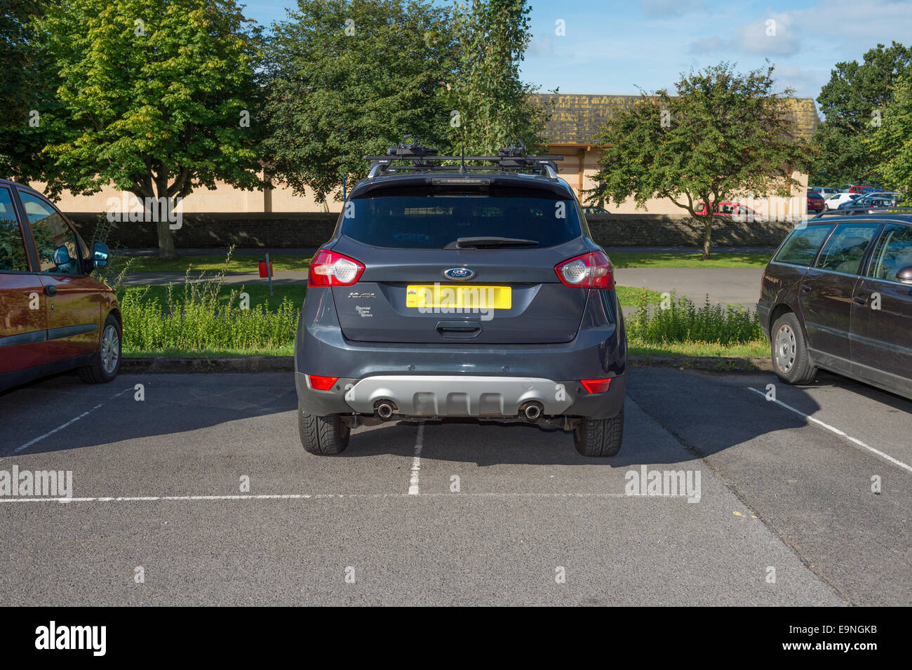 Bad Parking: A 4x4 car badly parked straddling two parking bays in a car park UK (number plate blurred) - Stock Image