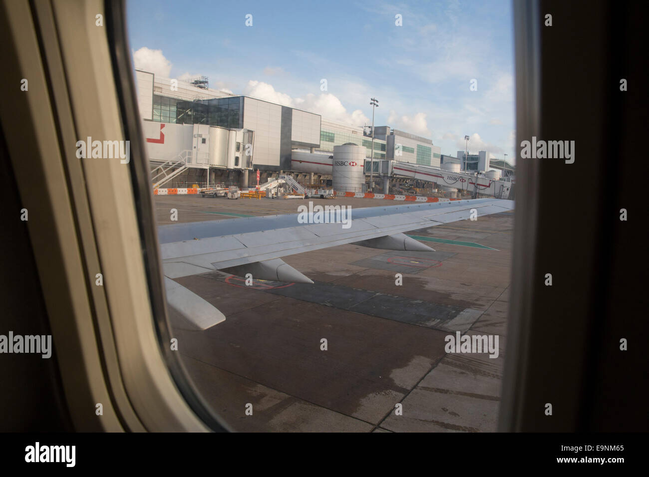 View from an aeroplane window of the plane's wing, airport buildings and tarmac. London Gatwick Airport. - Stock Image