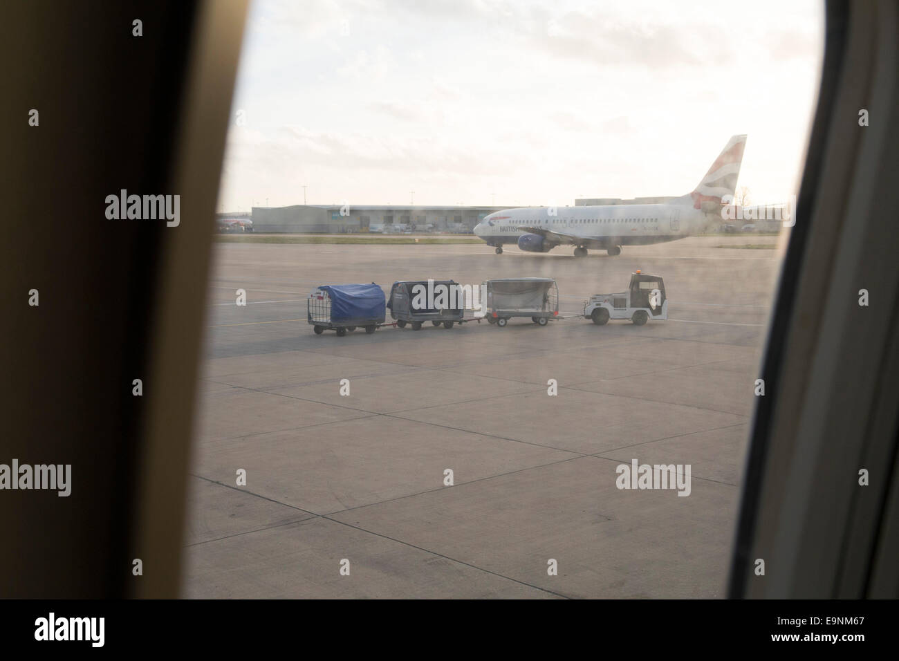View from an aeroplane window or baggage train, luggage trolleys and plane on the tarmac - Stock Image