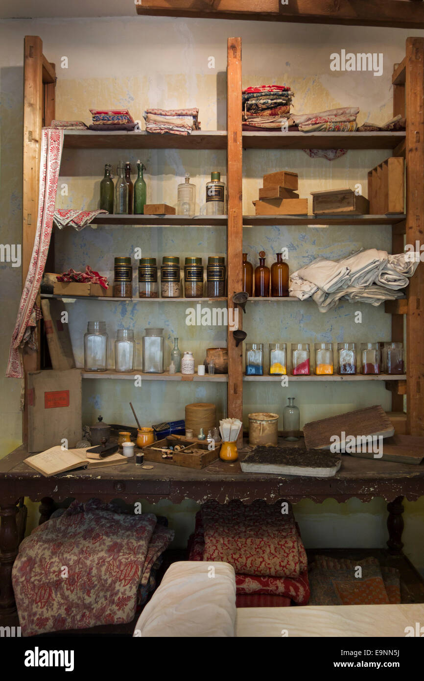 Glass jars with dyes on shelves in old workshop for printing patterns on fabric by using woodblocks - Stock Image