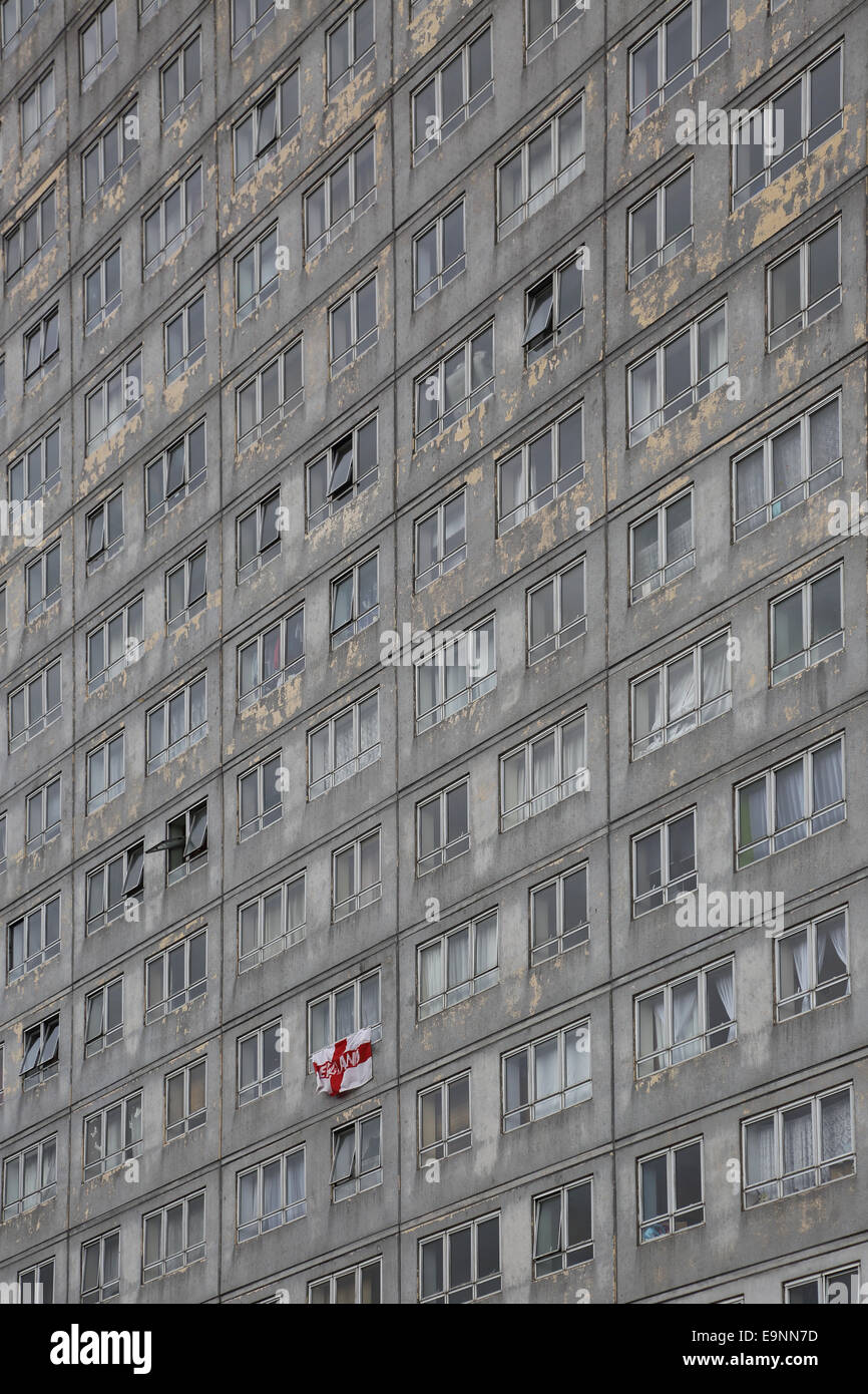 The face of a dilapidated residential tower block in Sutton, South London, UK showing peeling paint and an England - Stock Image