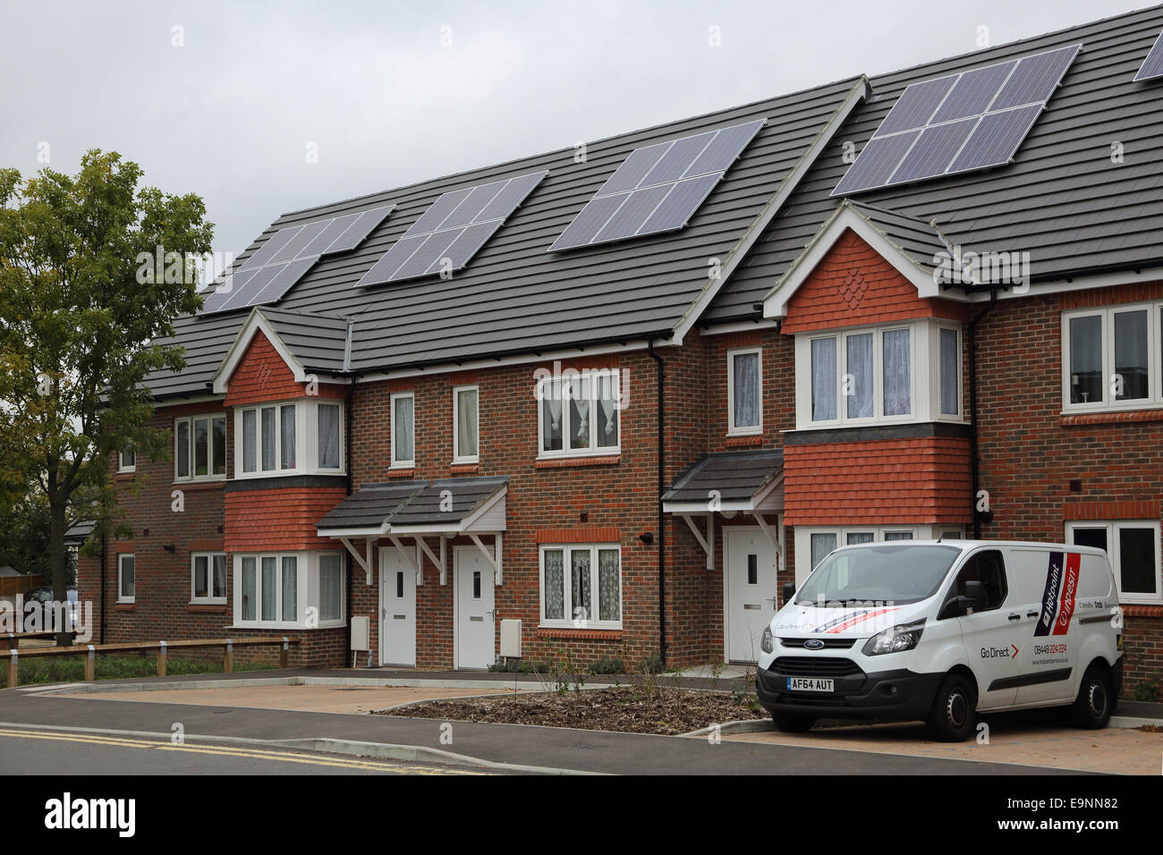 A new housing estate featuring solar PV panels installed on the pitched roof - Stock Image