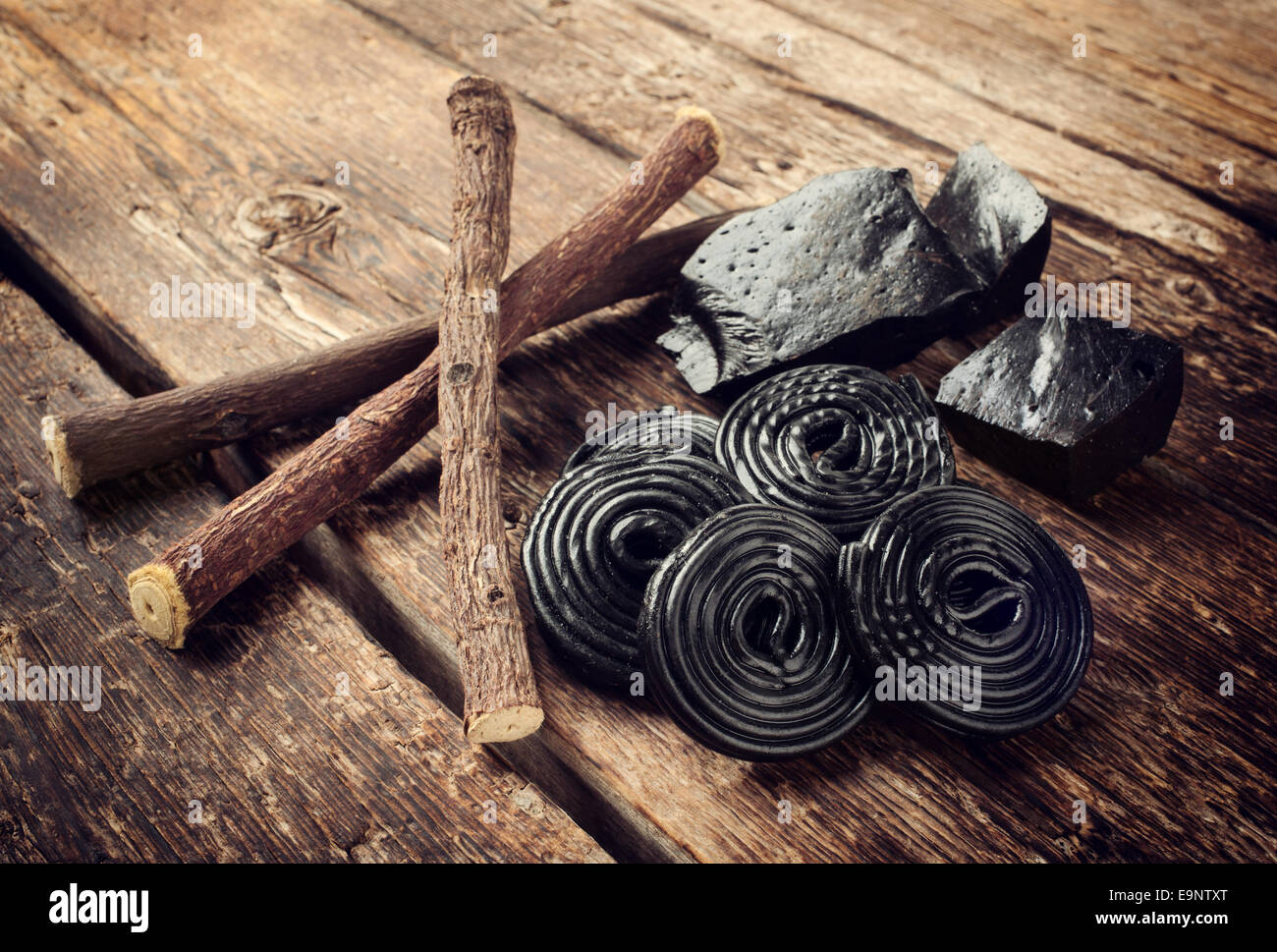 Production steps of licorice, roots, pure blocks and candy on wooden table - Stock Image