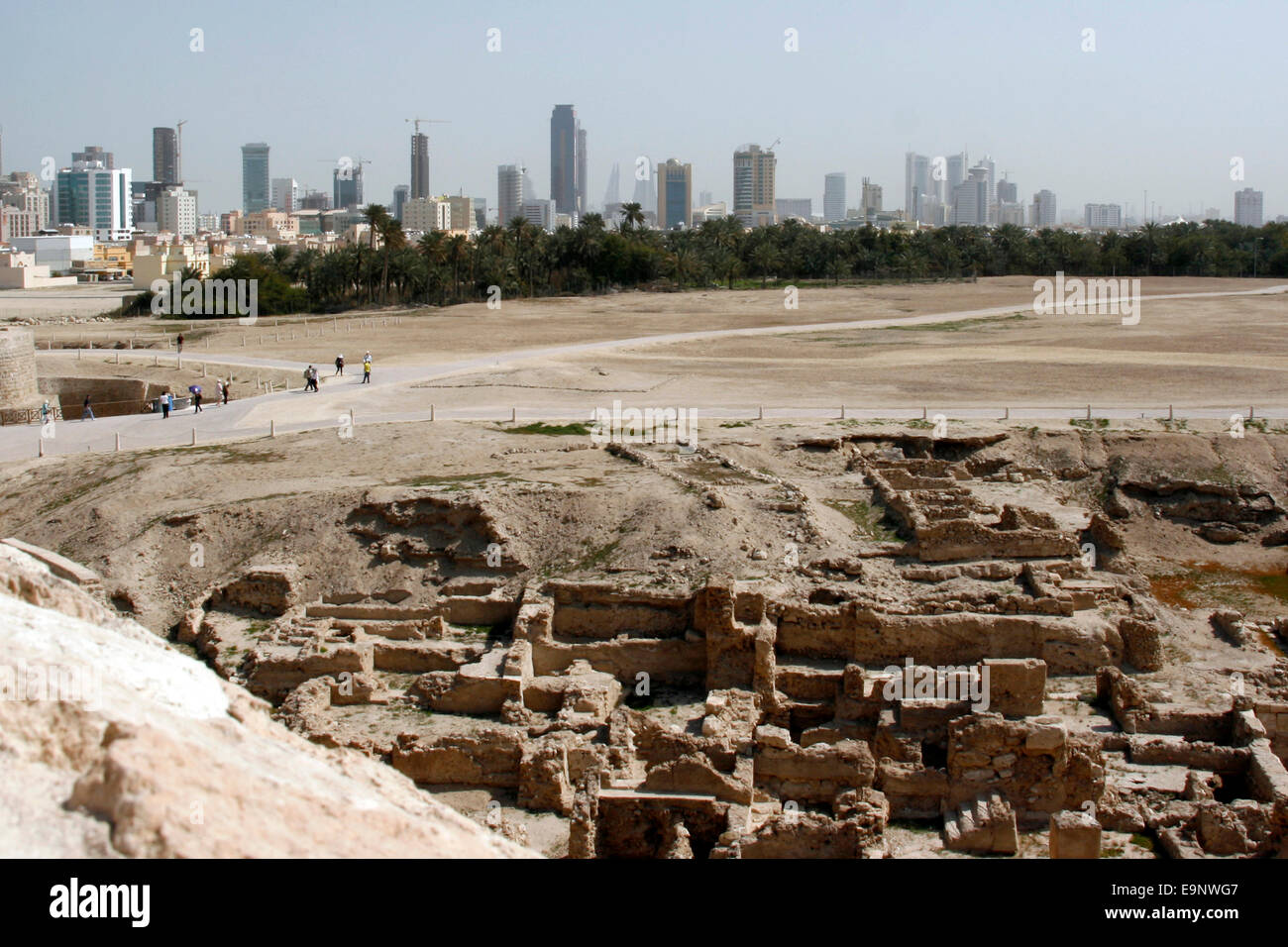 The ruins of Qala'at Bahrain, also known as the Portuguese Fort, with the towers of Manama, Bahrain in the background - Stock Image