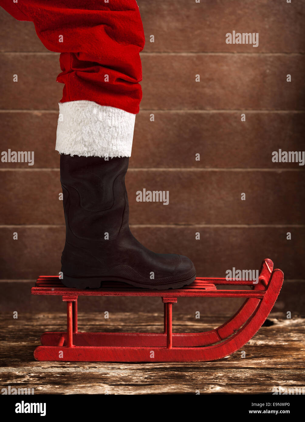 Wooden red sled with the boot of Santa Claus - Stock Image