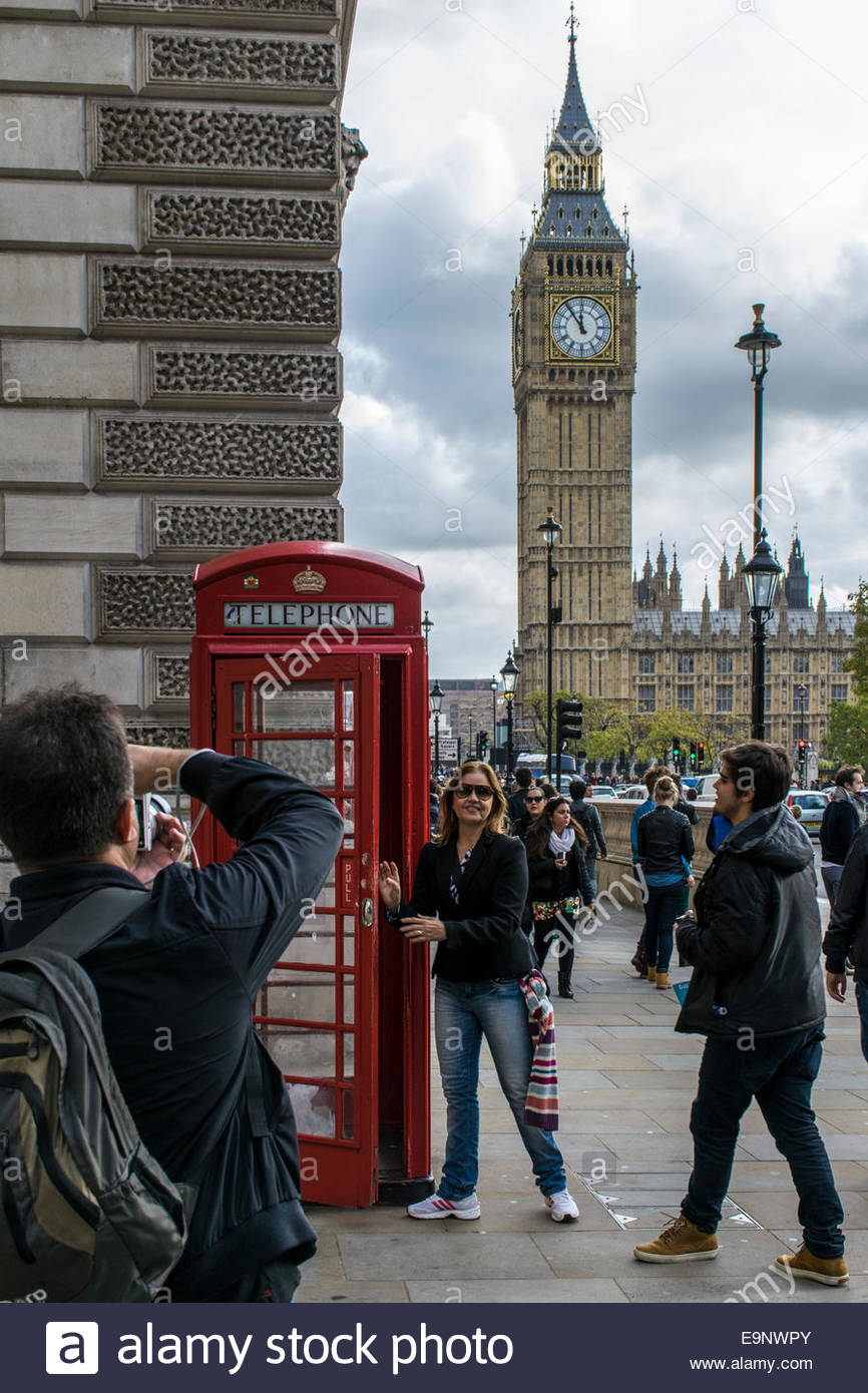 Tourists posing for a photograph by a red telephone box in London with Big Ben in the distance - Stock Image