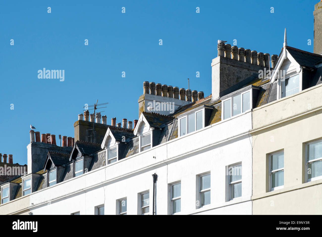 Rows of chimneys on top of tall houses in Weymouth Dorset UK - Stock Image