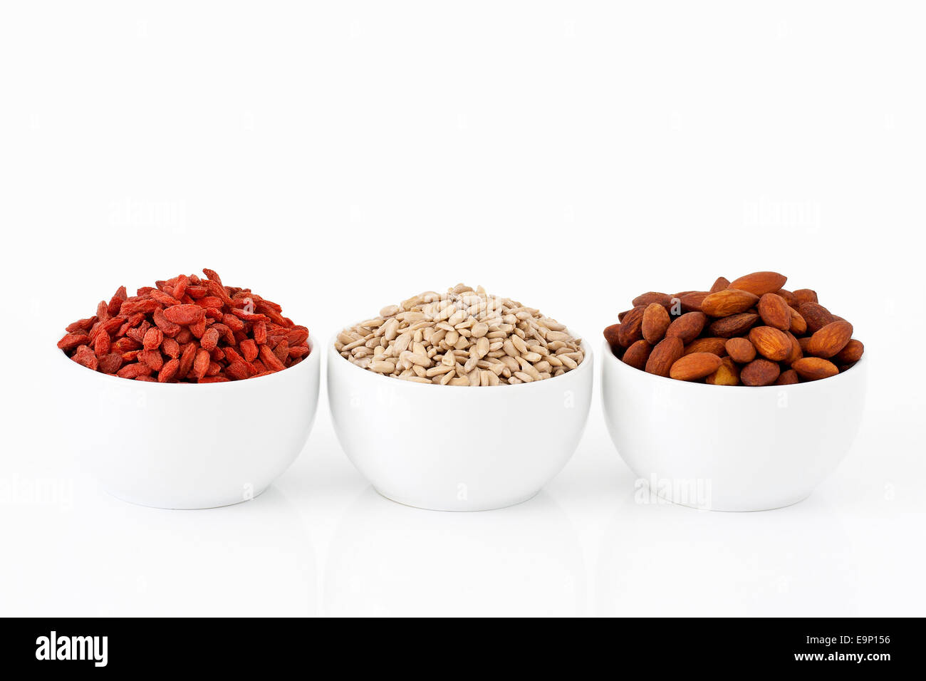 Almonds, sunflower seeds and goji berries on white background - Stock Image