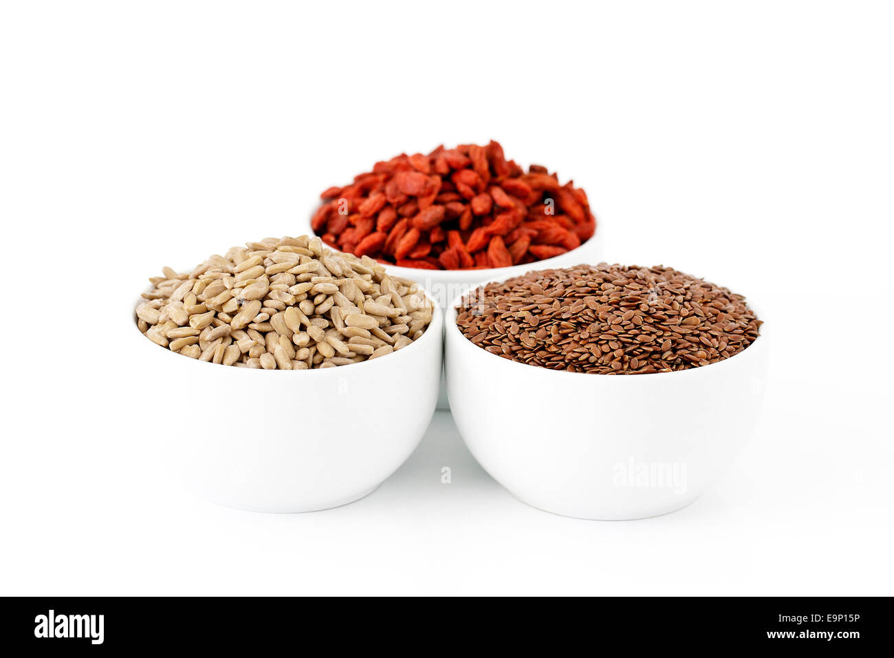 Flaxseeds, sunflower seeds and goji berries on white background - Stock Image