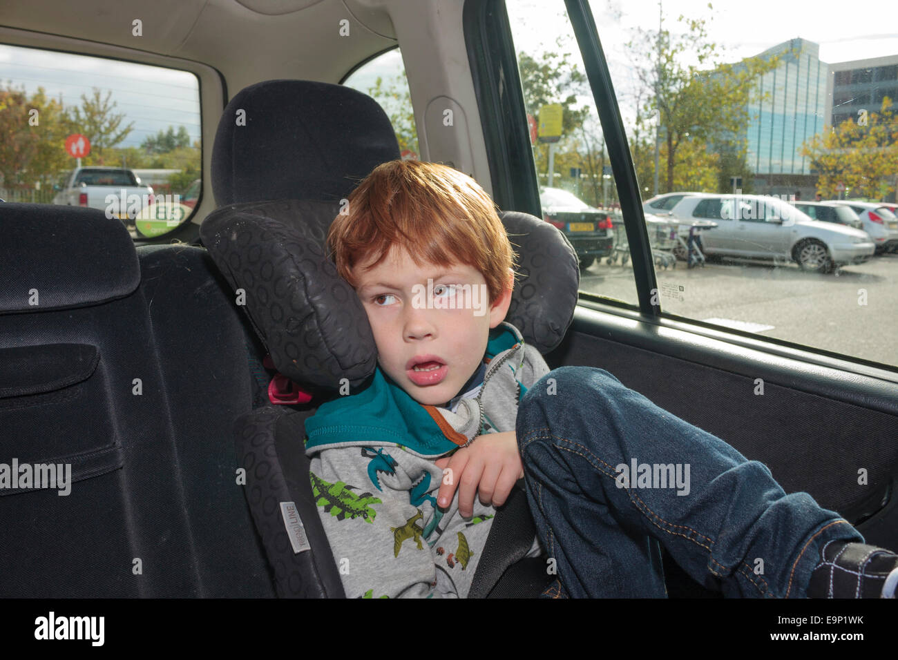 A Young Old Boy Looking Bored Sitting In Car Seat Parked At Supermarket Park