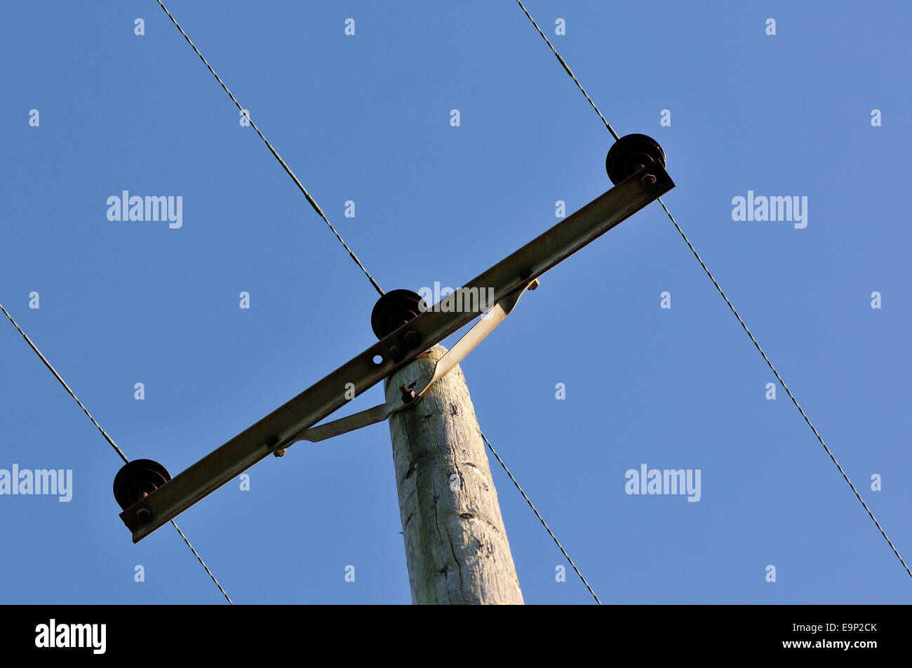 Rural Electricity powerlines suspended by wooden post - Stock Image