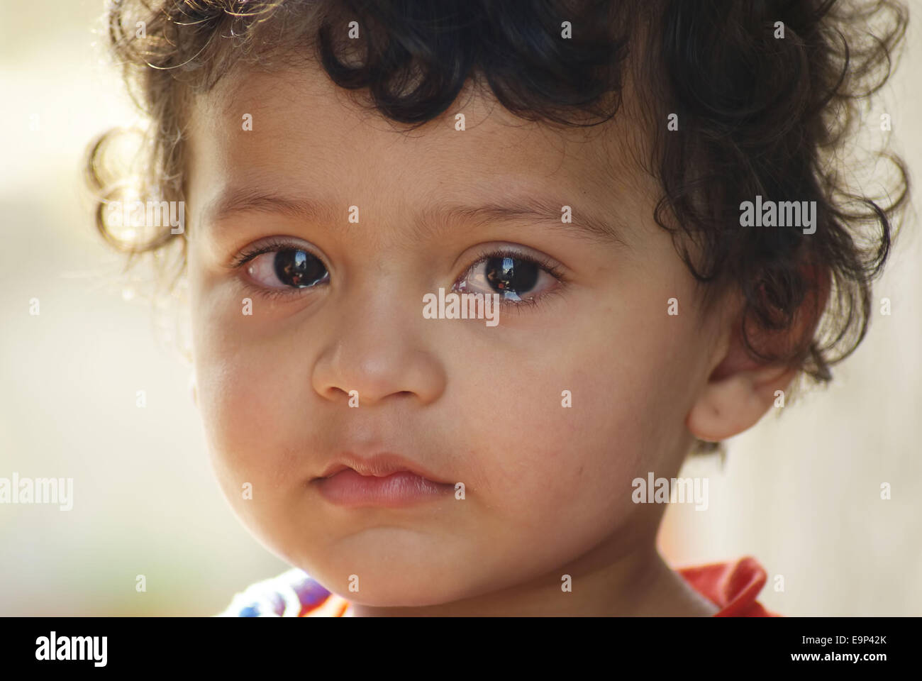 Sad Indian child with tears and curly hair looking at camera - Stock Image