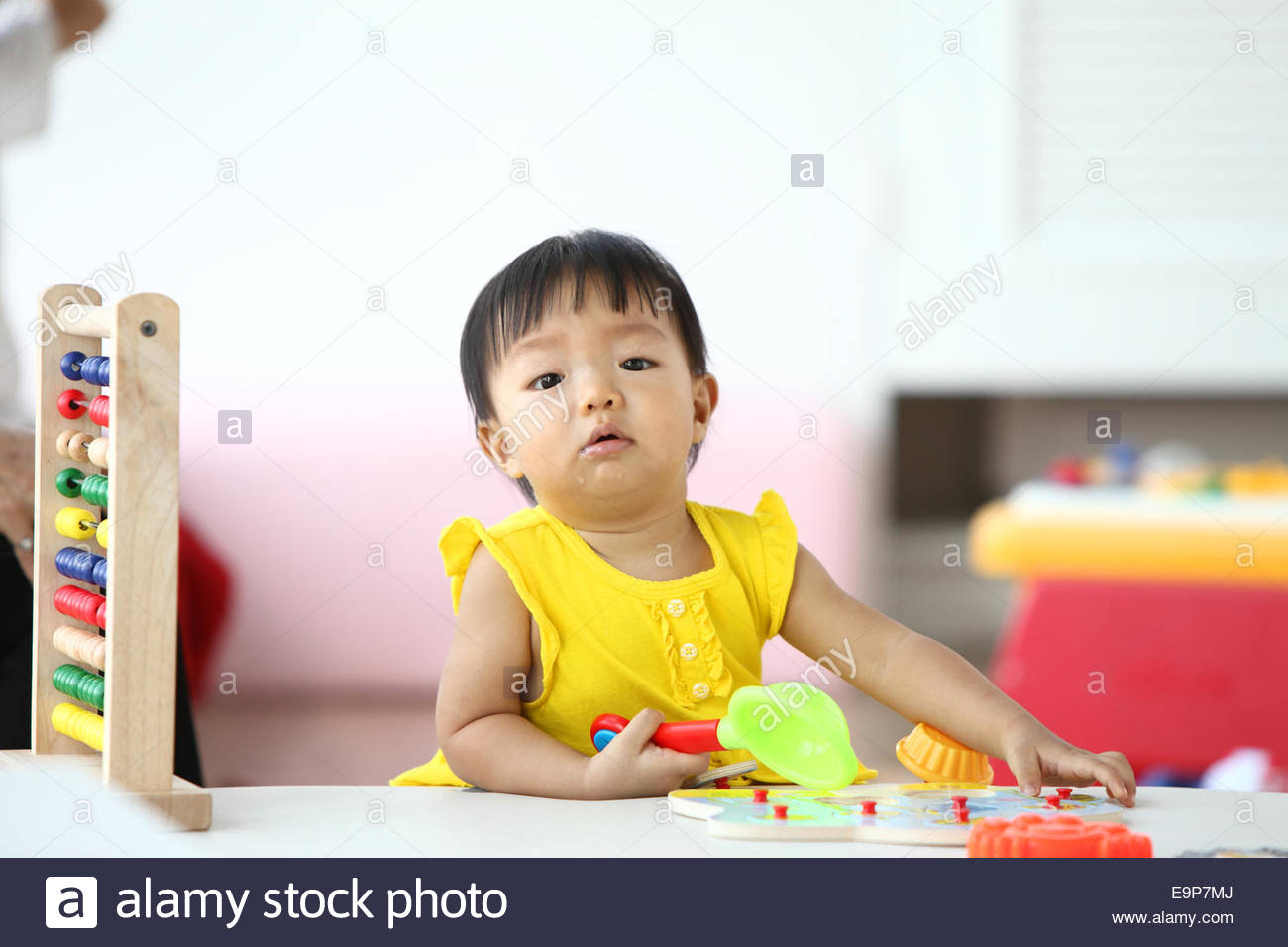 curious baby girl studying nursery room - Stock Image