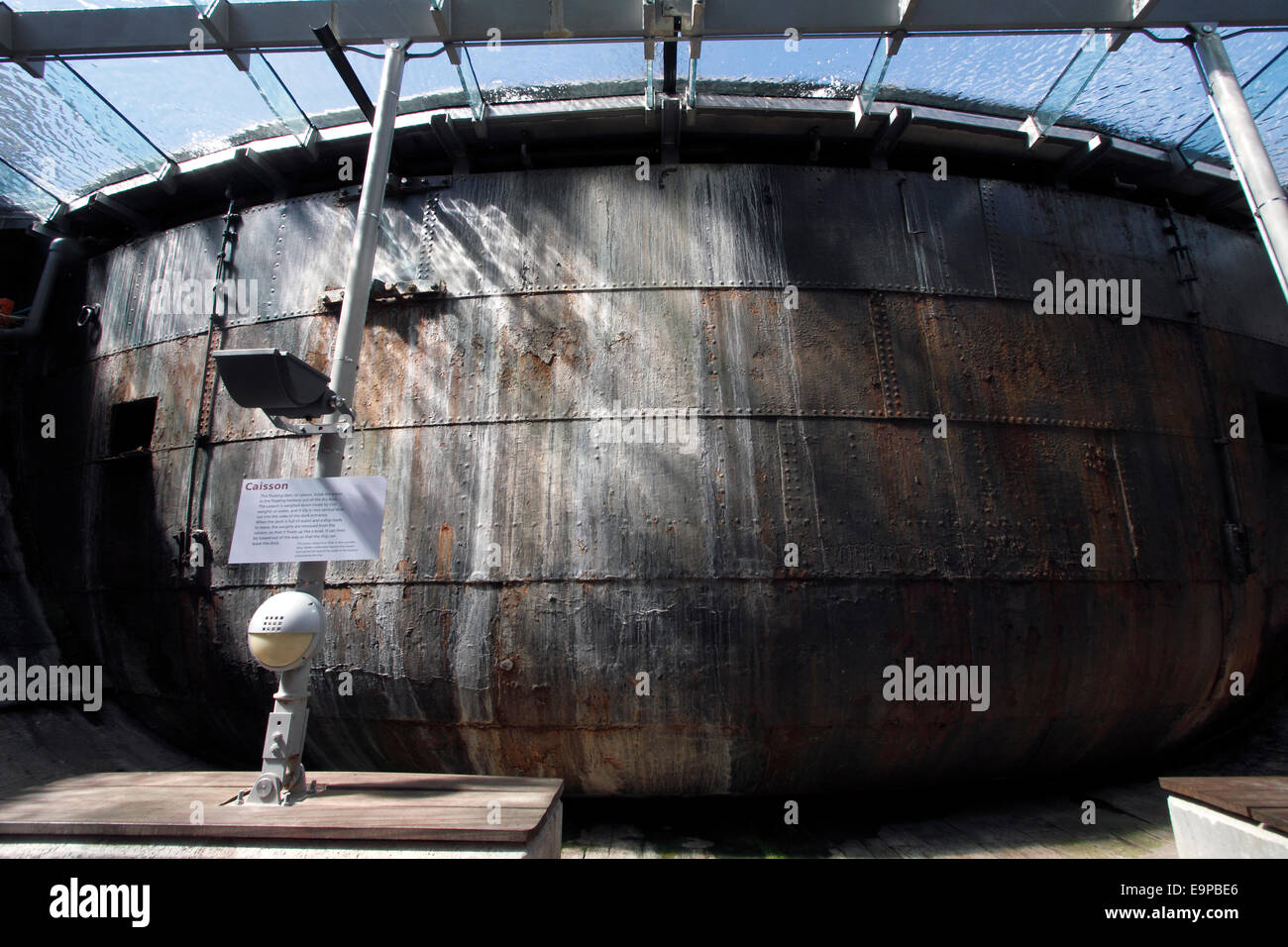 A floating dam or caisson that holds back water in a floating harbour from the dry dock.  the caisson is held down - Stock Image