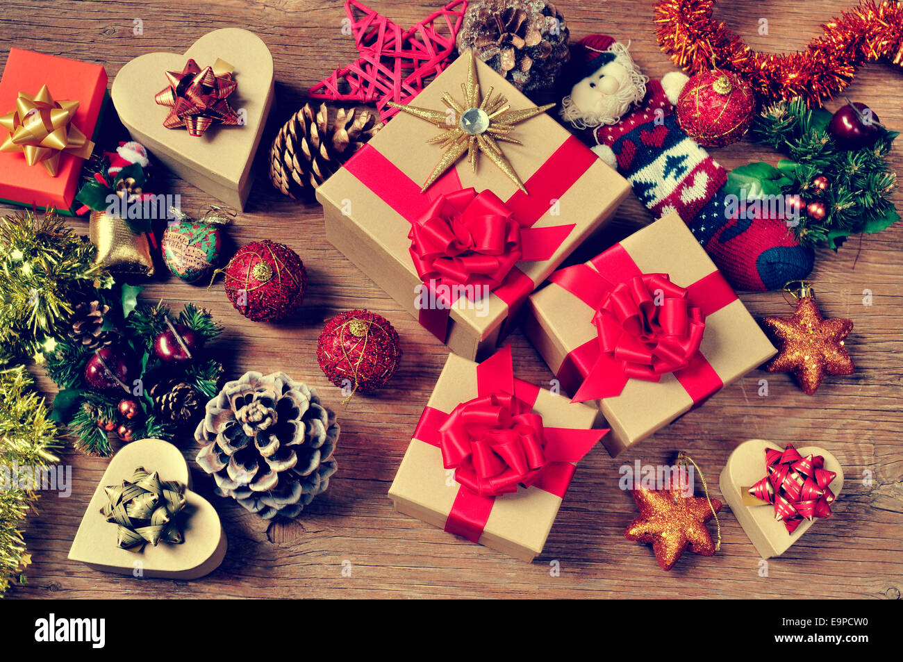 a pile of gifts and christmas ornaments, such as christmas balls, stars and tinsel, on a rustic wooden table - Stock Image