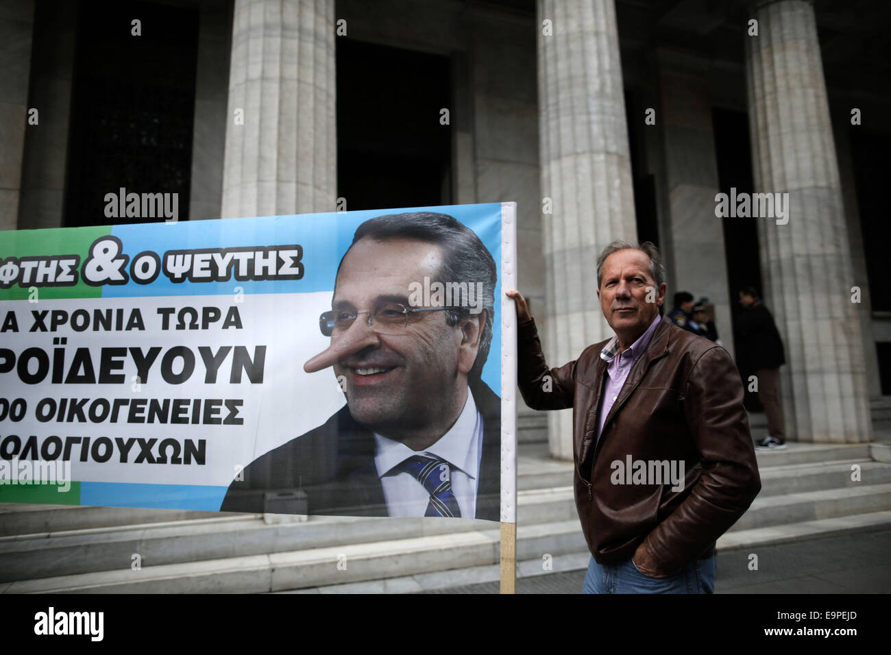 Thessaloniki, Greece. 31st Oct, 2014. An elderly small bondholder holds a banner with a caricature of Greece's - Stock Image