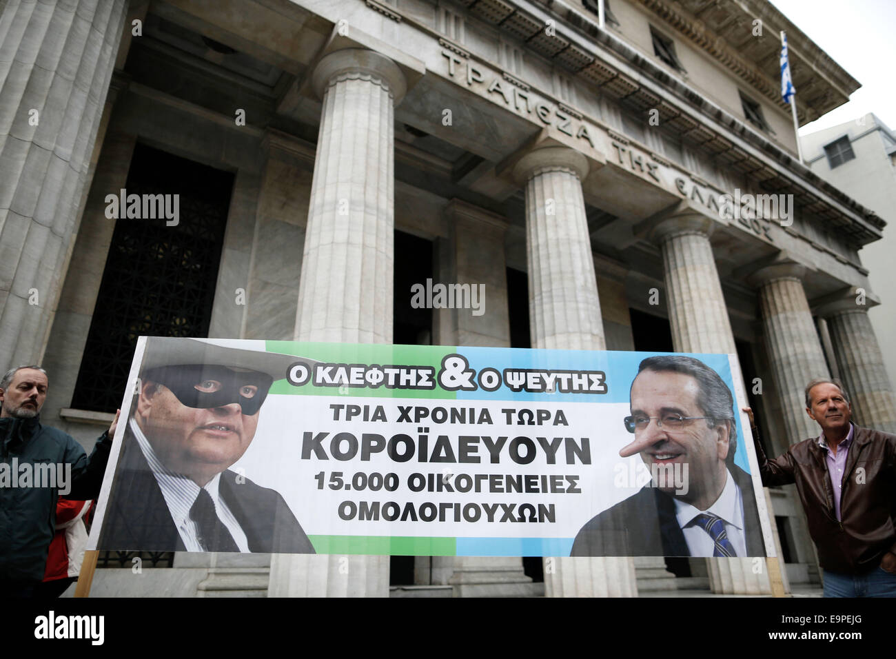 Thessaloniki, Greece. 31st Oct, 2014. Elderly small bondholders hold a banner with  caricatures of Greece's - Stock Image