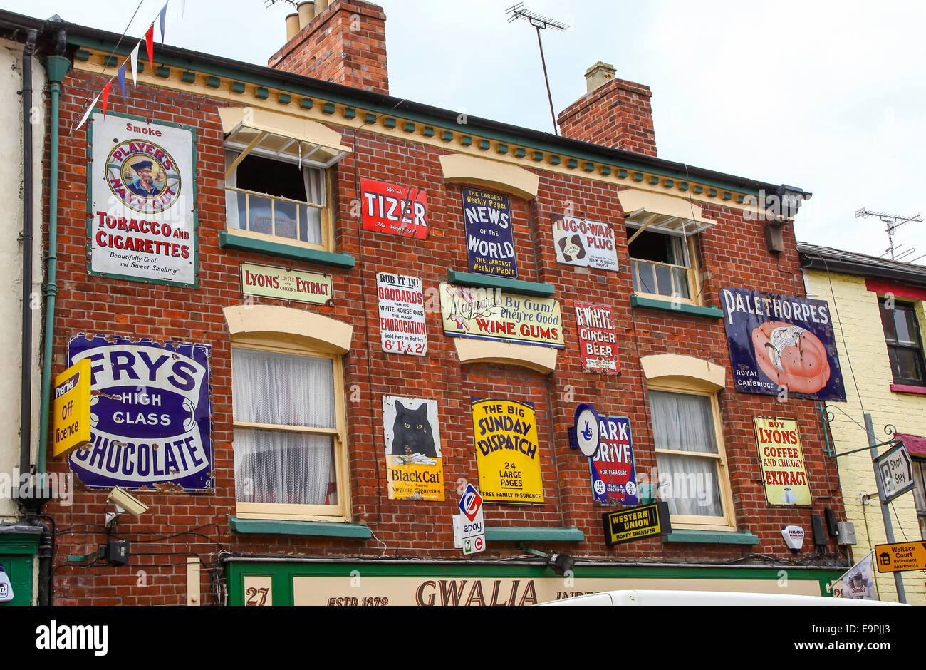 Old enamel advert adverts advertising signs on Gwalia shop frontage Ross on Wye Herefordshire England UK - Stock Image