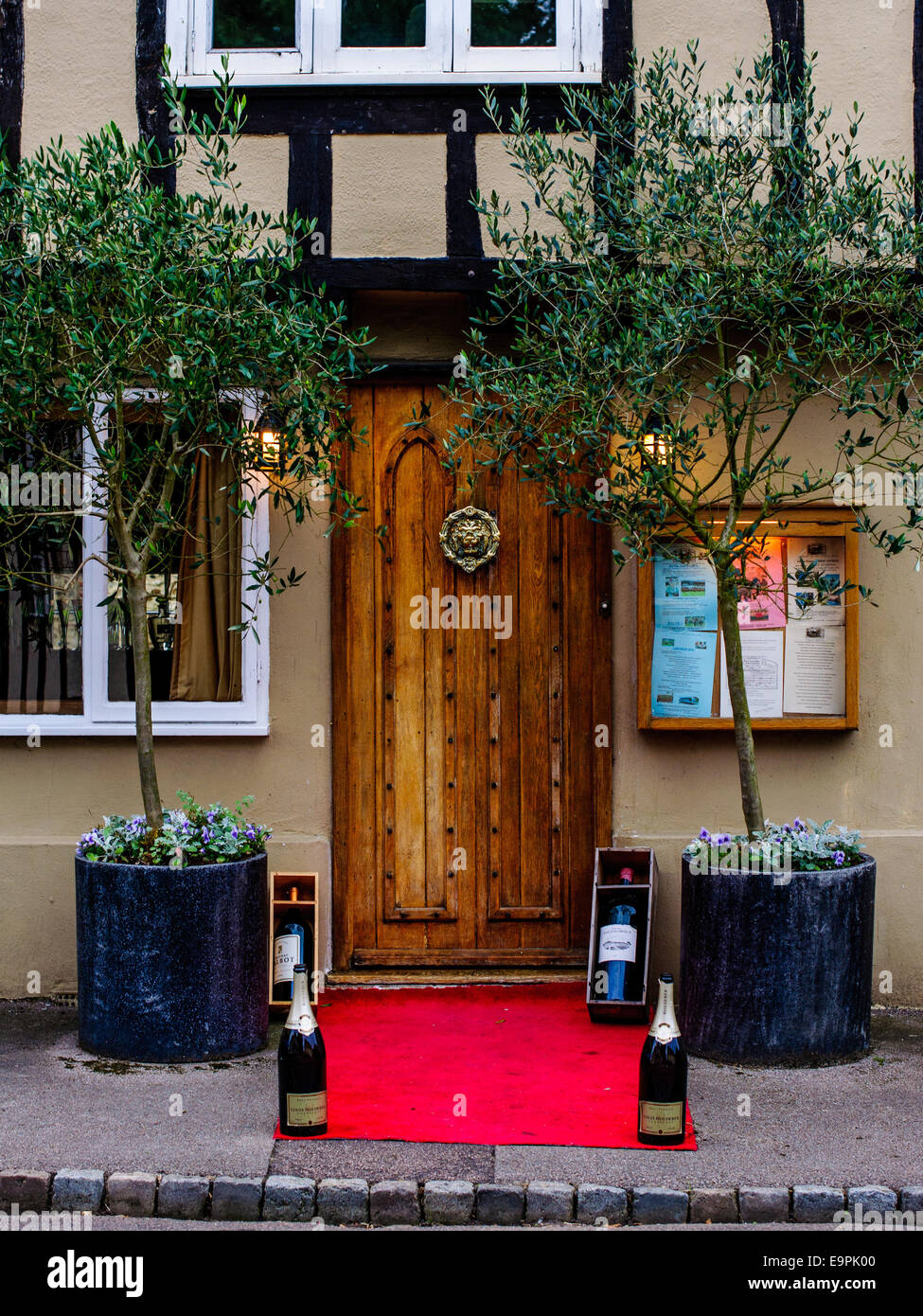 Front wooden door from nice restaurant with red carpet Champagne bottles. Essex - Stock Image