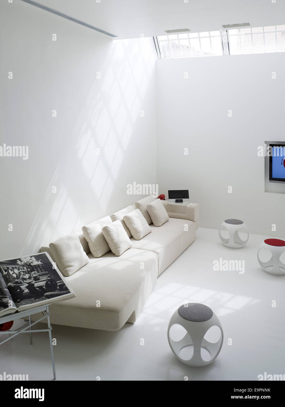 White living room with small white circular occasional tables and ...