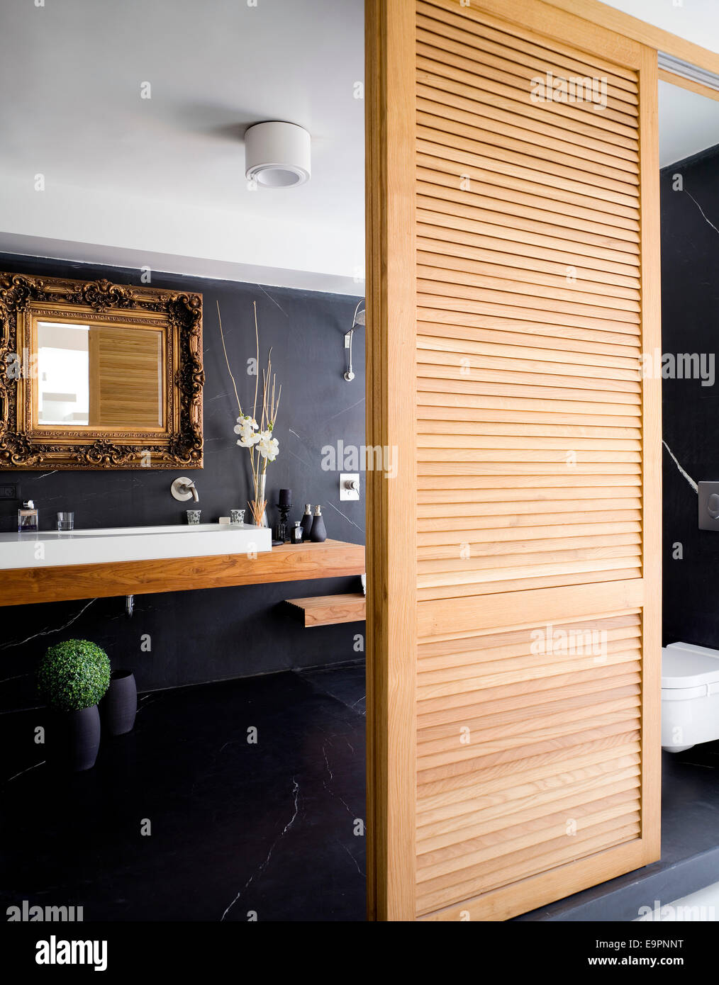 Bathroom behind sliding wooden louvered doors in Hilit home, Israel ...