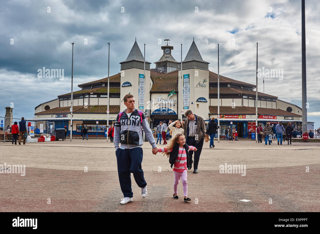 Bournemouth Pier Family Amusements on an overcast day, with many visitors nearby. Father and daughter in foreground. - Stock Image