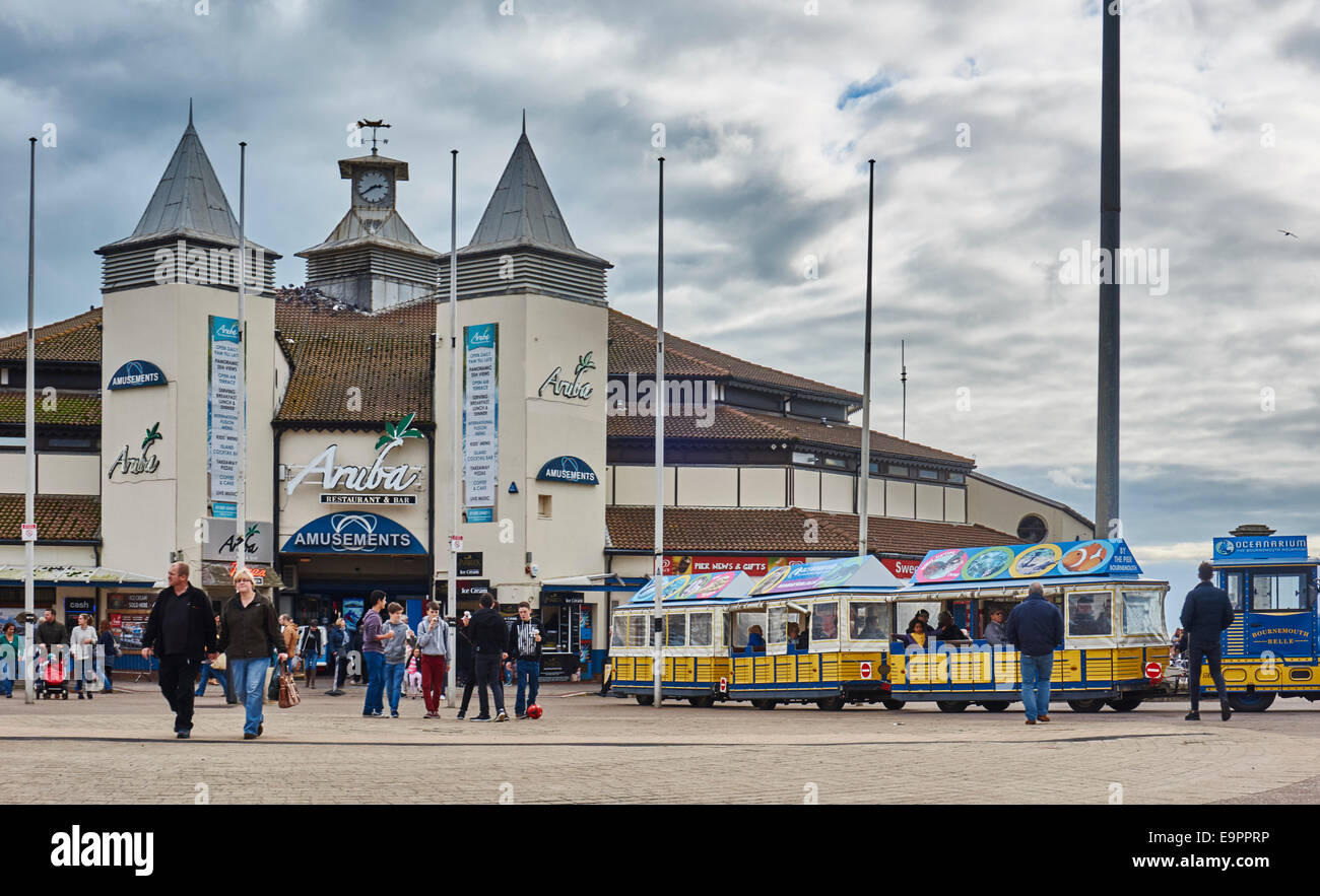 Bournemouth Pier Family Amusements on an overcast day, with many visitors and the 'Bournemouth Belle' train. - Stock Image