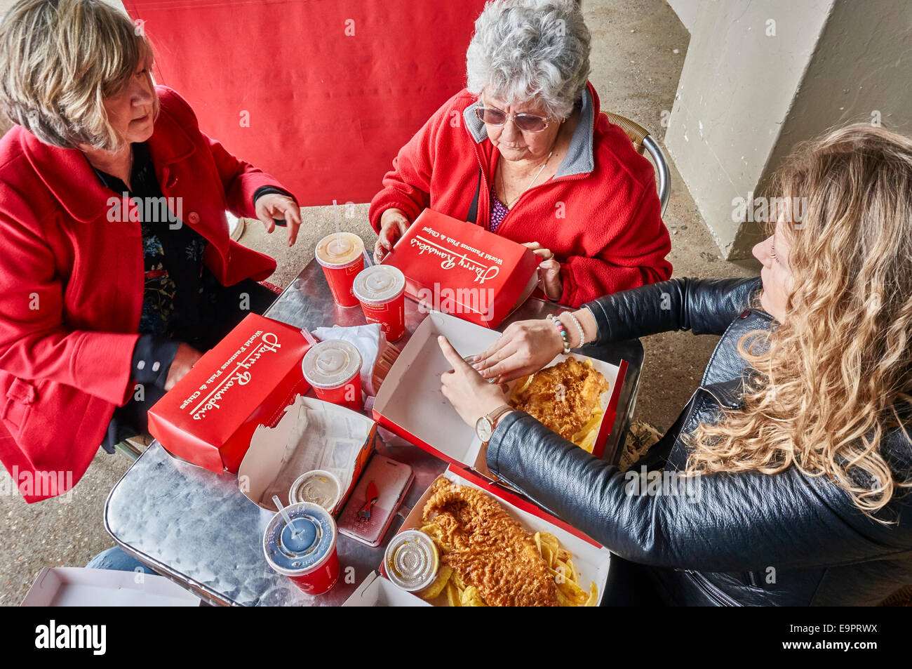 Three generations of women ready to eat fish and chips, sitting at a table, outside Harry Ramsdens next to Bournemouth - Stock Image