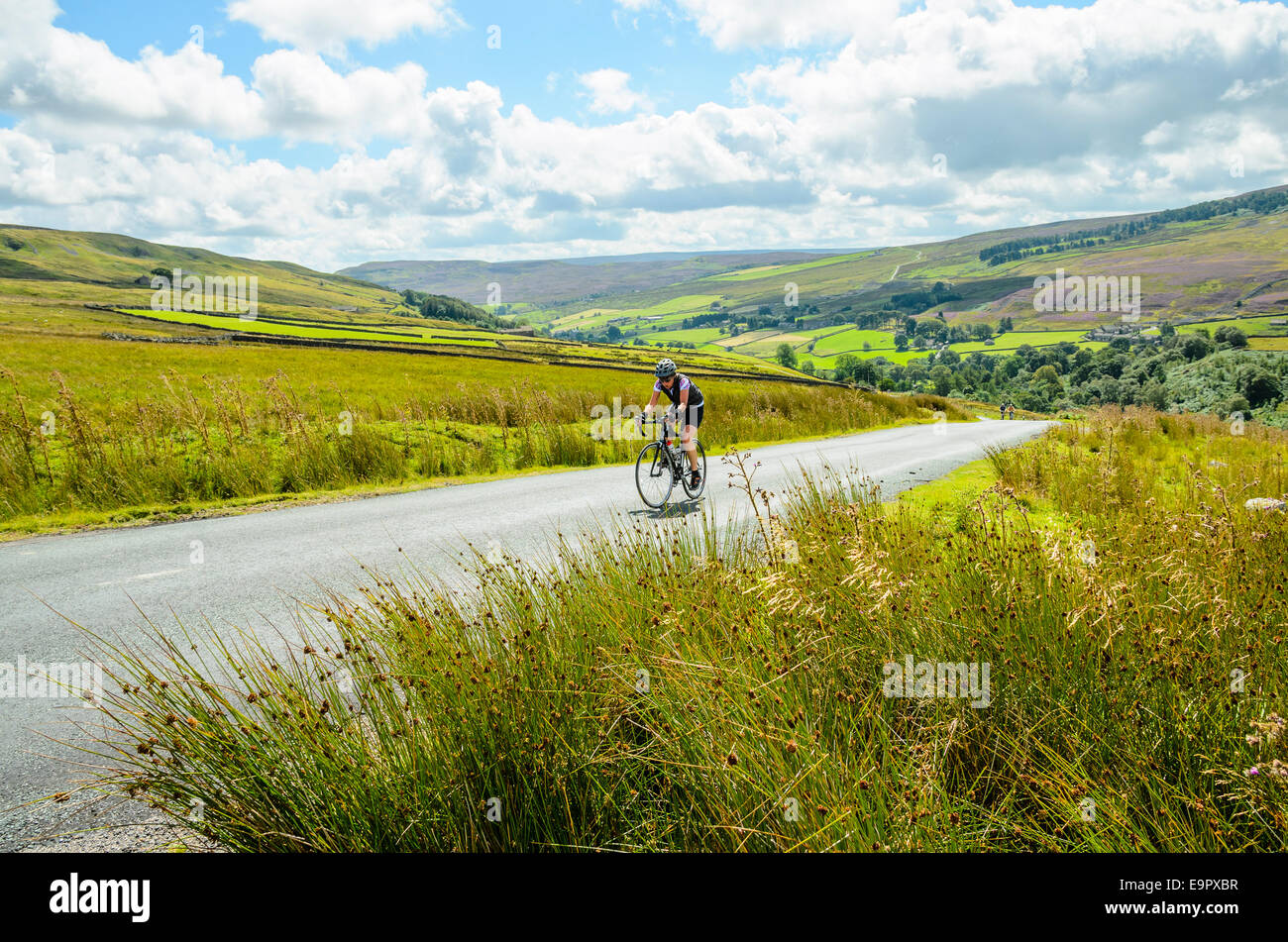 Female cyclist climbing The Stang in the Yorkshire Dales - Stock Image