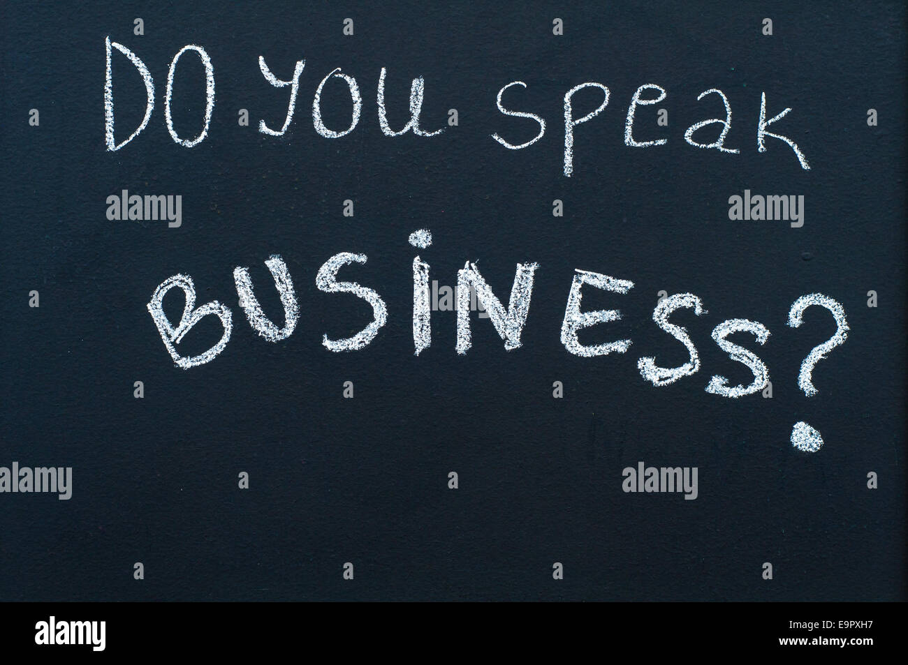 Do you speak business? message written with white chalk on blackboard - Stock Image