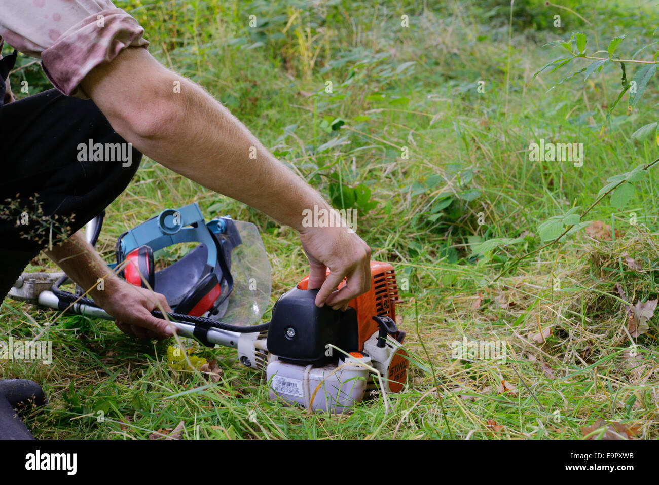 Man priming a 2 stroke petrol engine attached to a strimmer or brushcutter, Wales, UK. - Stock Image