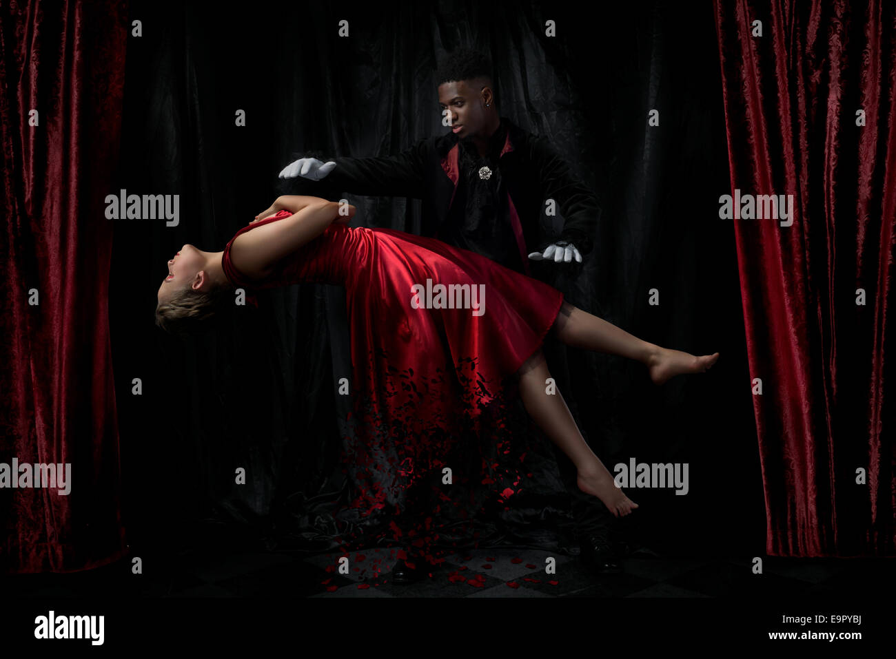 Magician performing levitation act on a stage - Stock Image