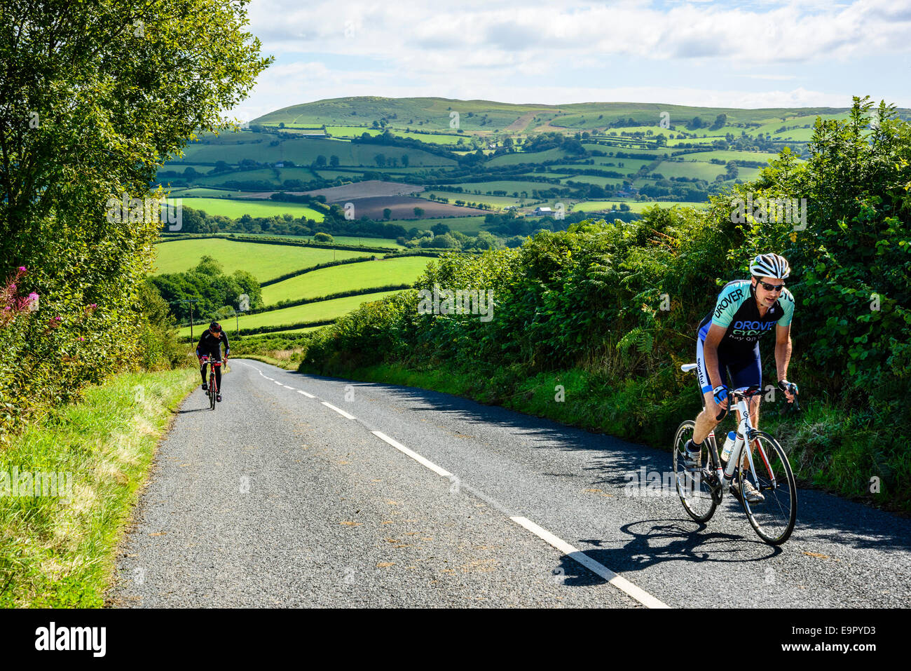 Cyclists climbing a hill on the B4594 Powys Wales - Stock Image