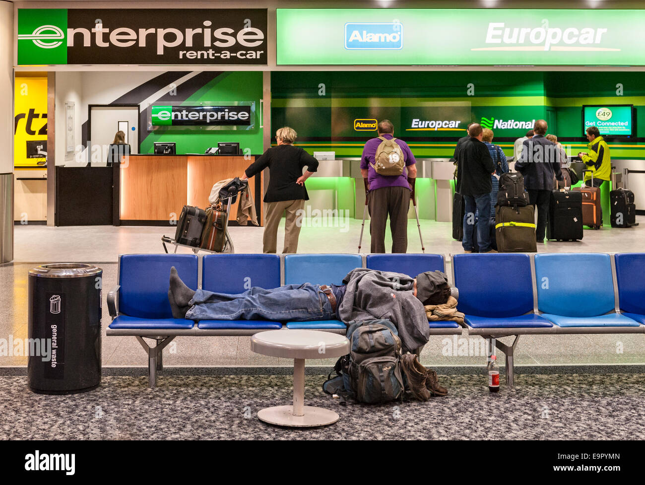 Early morning at Gatwick airport, UK. A sleeping backpacker stretched along a row of seats in front of the car hire - Stock Image
