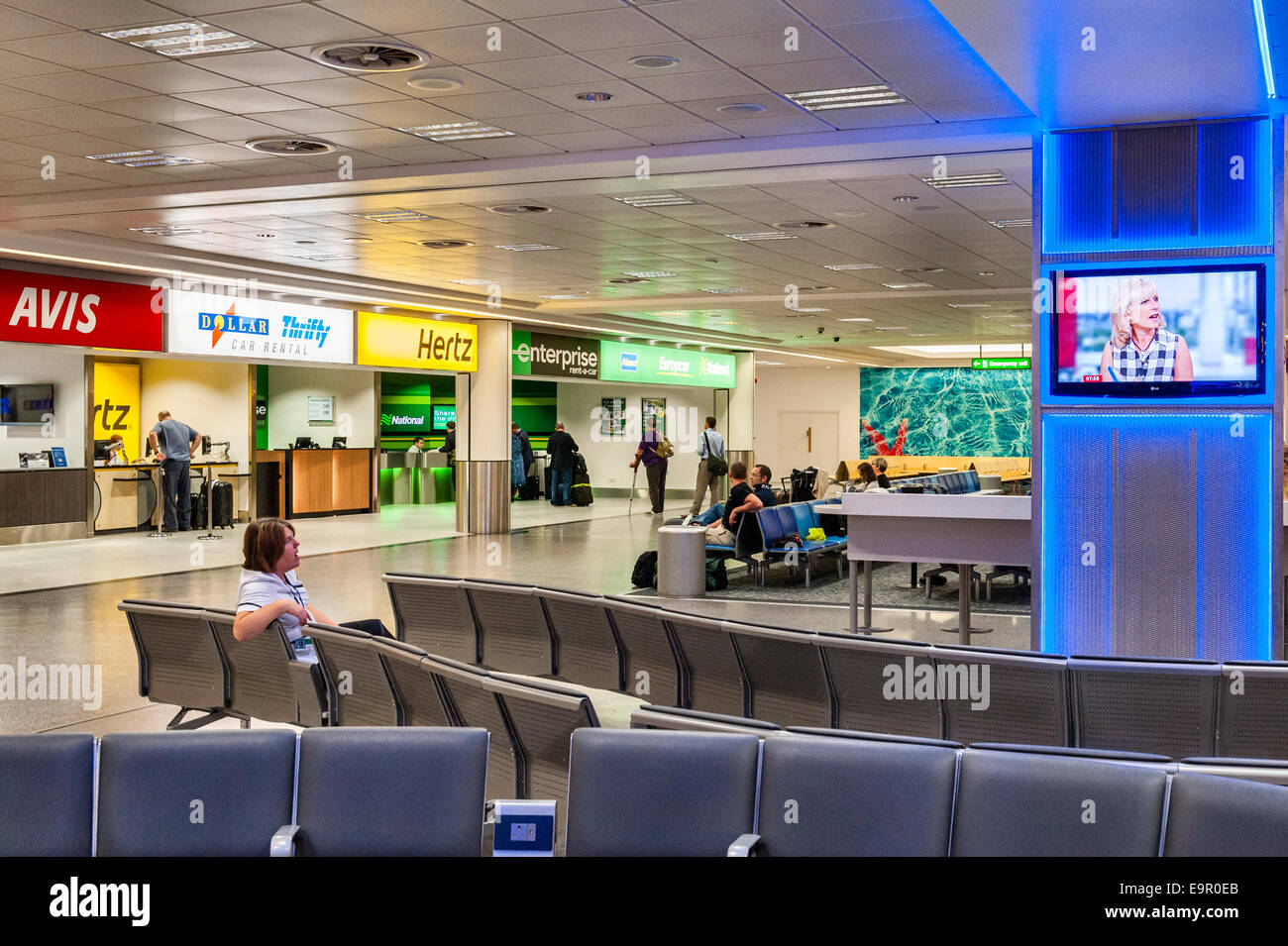 Gatwick airport, UK. A bored cleaner watching TV yawns on her early morning shift - Stock Image