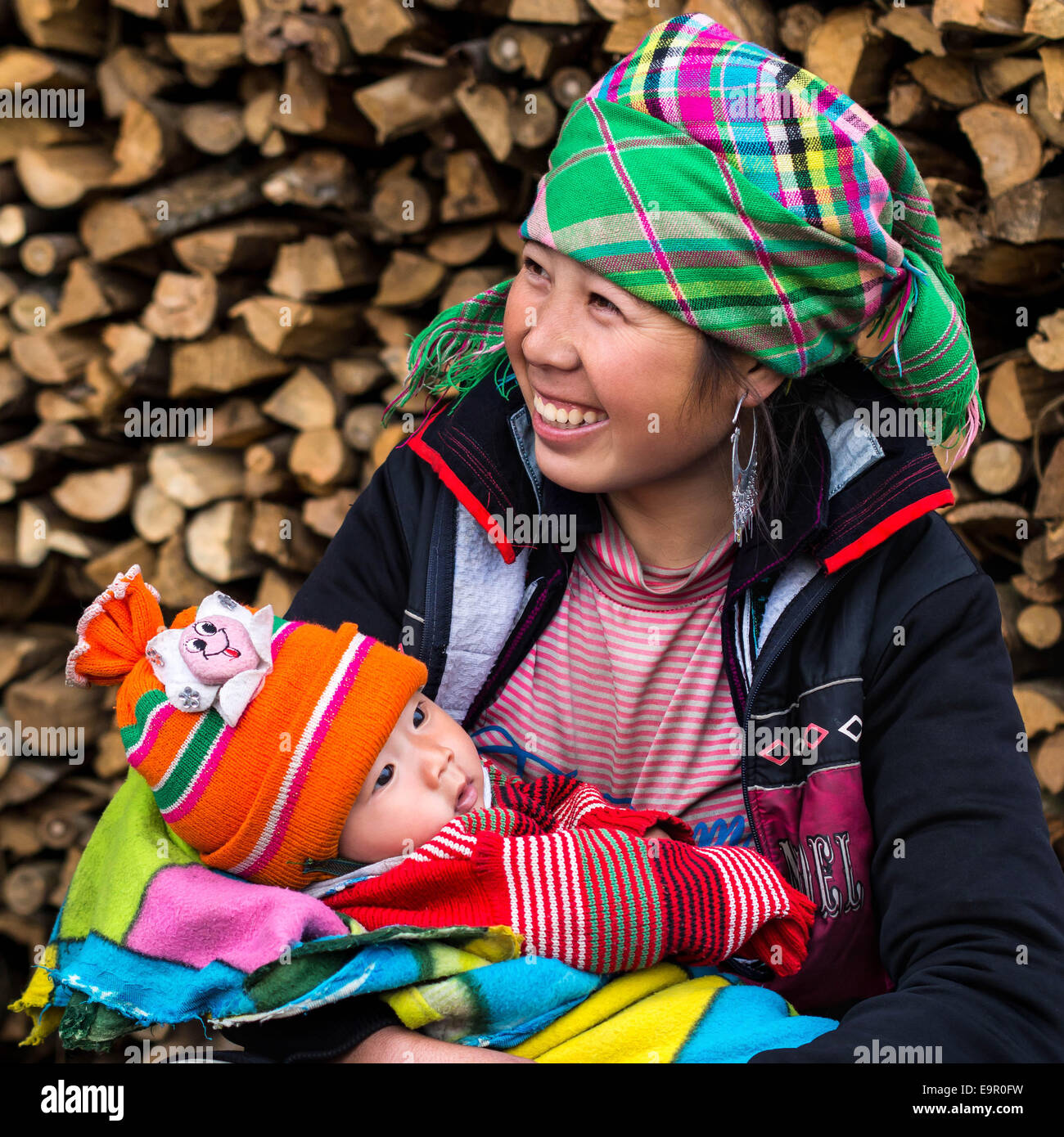 Happy Hmong woman with baby, smiling, sitting outside at Ta Van village near Sapa, Lao Cai Province, North Vietnam. - Stock Image