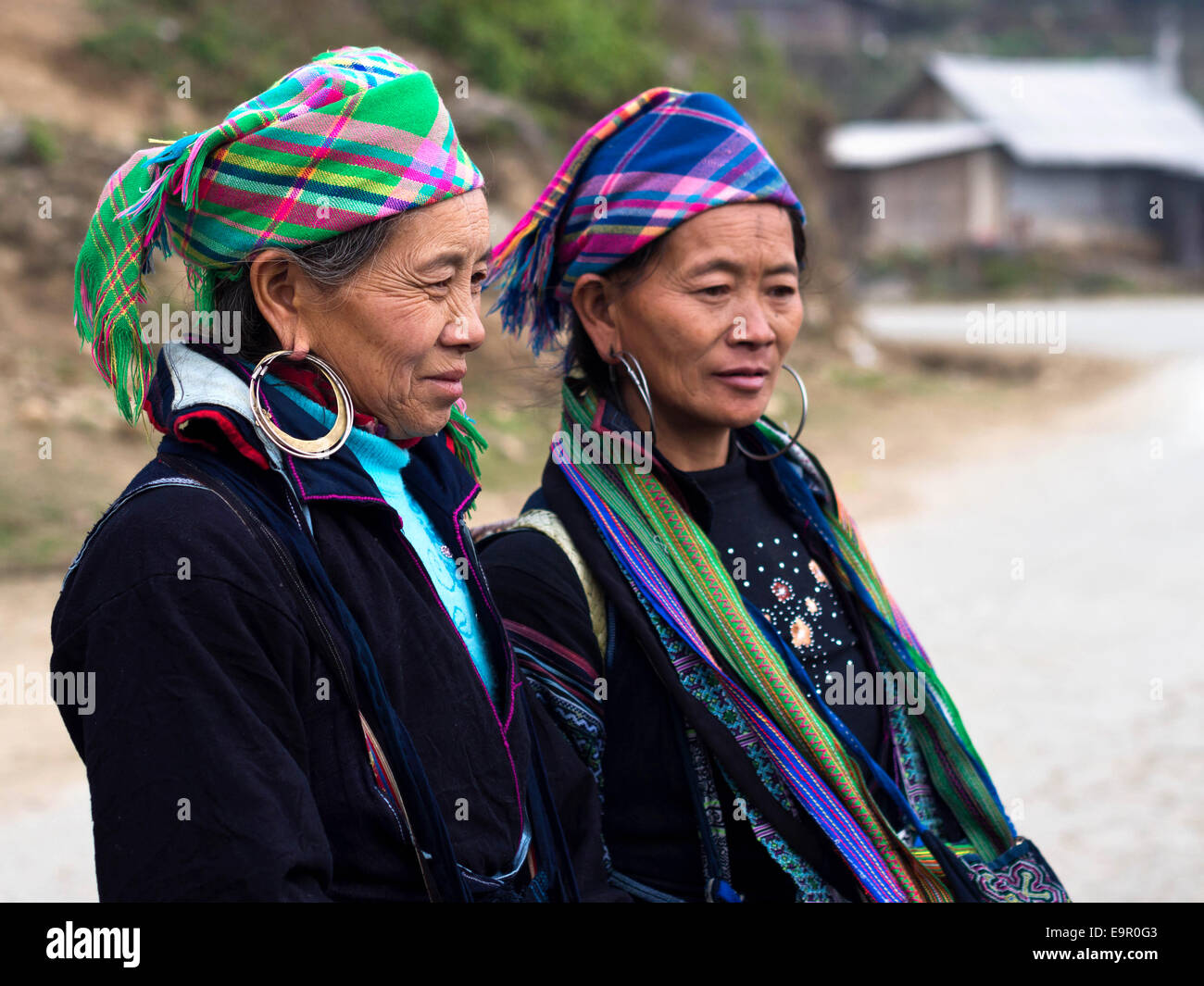 Black Hmong women wearing traditional attire and jewelry standing on the trail to Ta Van village, near Sapa Town, - Stock Image